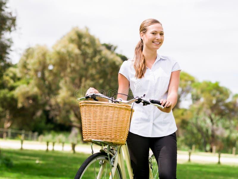 Den härliga unga blonda kvinnan med cykeln parkerar in royaltyfri bild