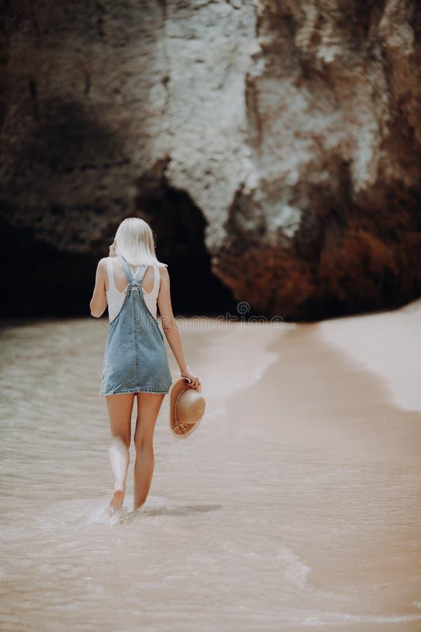 Den härliga unga blonda kvinnaturisten som går på stranden med, vaggar på den härliga stranden nära havet royaltyfri foto
