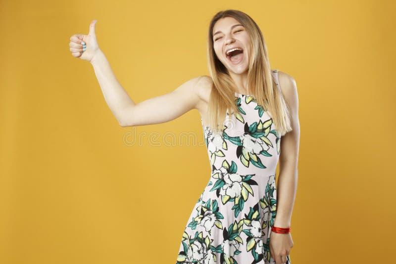 Den härliga unga blonda lyckliga oken för flickavisninghanden undertecknar över yello royaltyfria bilder