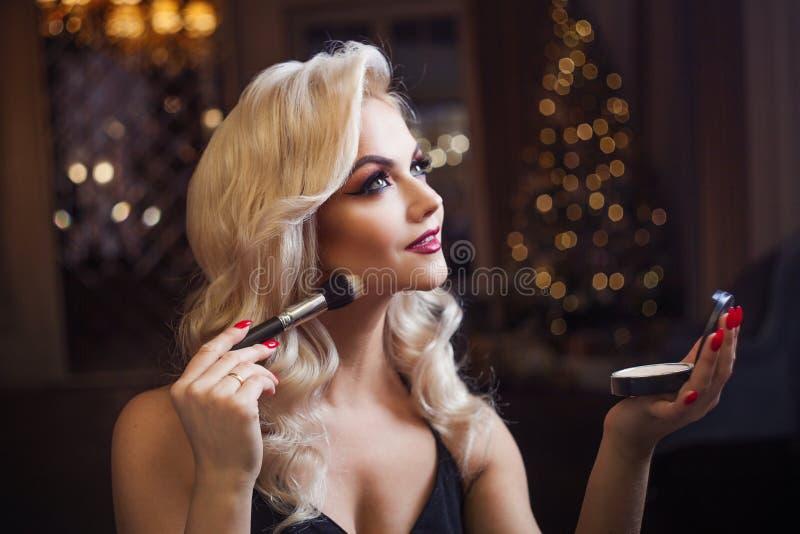 Den härliga unga blondinen gör en ljus feriemakeup Glamoröst smink En attraktiv ung kvinna använder pulver royaltyfri bild