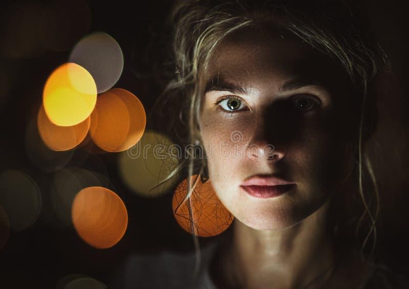 Den härliga unga blondinen i nattljuset ser kameran Närbildstående, bokeheffekt royaltyfri fotografi