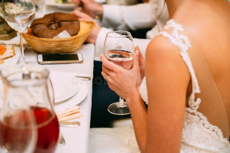 Den härliga unga bruden i den vita klänningen lyftte playfully ett exponeringsglas av champagne på bröllop och önskar att göra et fotografering för bildbyråer