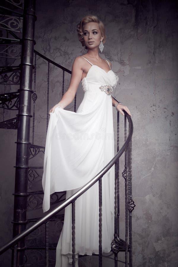 Den härliga unga bruden i en vit klänning står på en spiraltrappuppgång gifta sig för trappa för stående för brudbegreppsklänning royaltyfri bild
