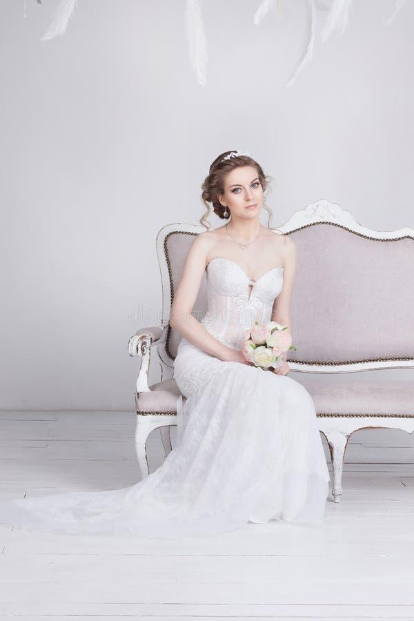 Den härliga unga bruden i ett lyxigt snör åt bröllopsklänningen Hon sitter på en vit tappningsoffa arkivfoton