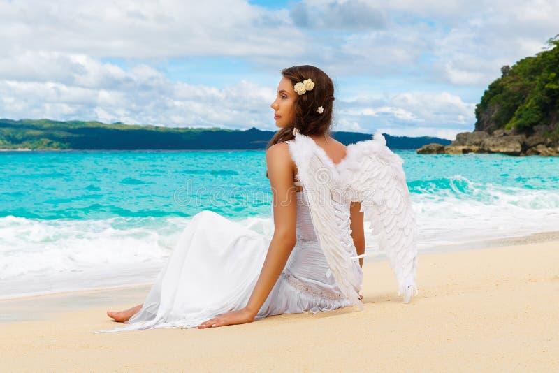 Den härliga unga bruden med ängel påskyndar på havskusten Tropica royaltyfri bild