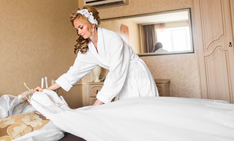 Den härliga unga bruden med bröllopmakeup och frisyren i sovrum, den attraktiva nygift personkvinnan har den sista förberedelsen  royaltyfria foton