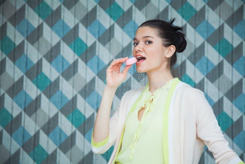 Den härliga unga brunettkvinnan äter franska makron royaltyfri foto