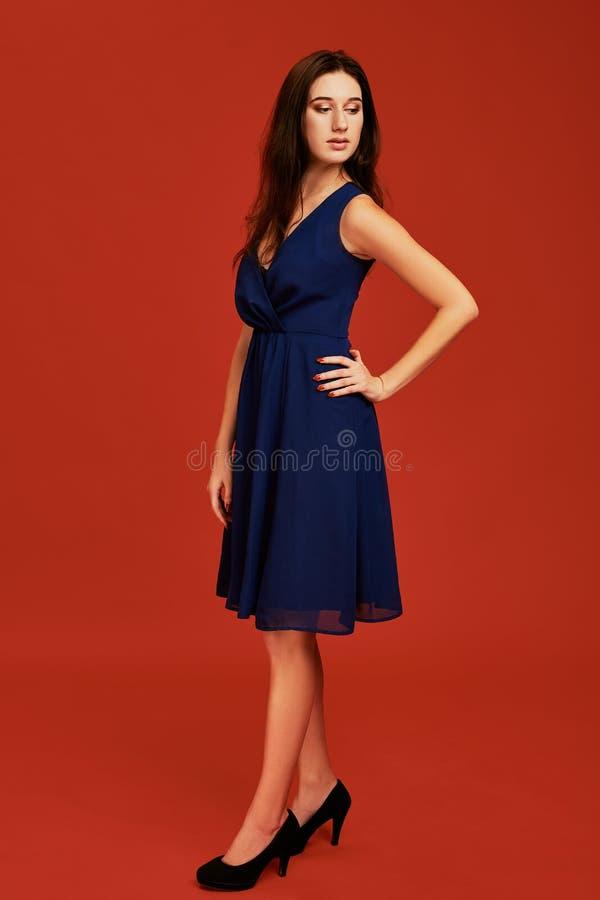 Den härliga unga brunettkvinnan i elegant blå coctailklänning och svarta höga häl poserar för kameran royaltyfri fotografi
