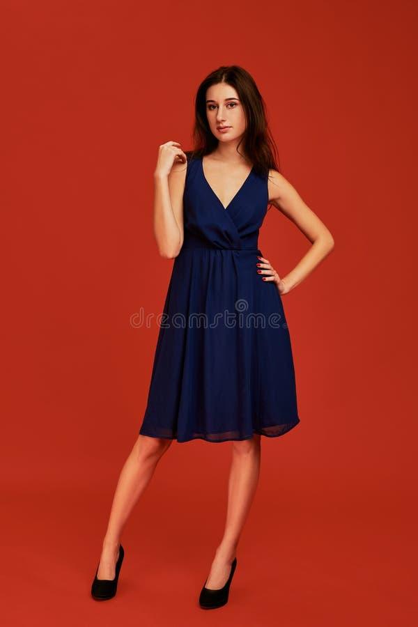 Den härliga unga brunettkvinnan i elegant blå coctailklänning och svarta höga häl poserar för kameran arkivfoto