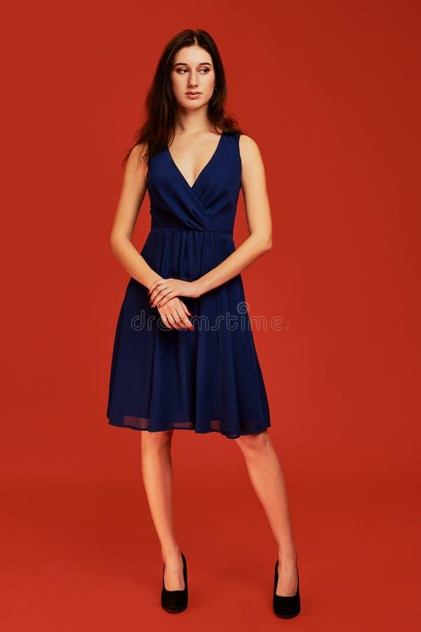 Den härliga unga brunettkvinnan i elegant blå coctailklänning och svarta höga häl poserar för kameran arkivbild