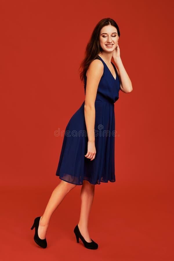 Den härliga unga brunettkvinnan i elegant blå coctailklänning och svarta höga häl poserar för kameran royaltyfria bilder