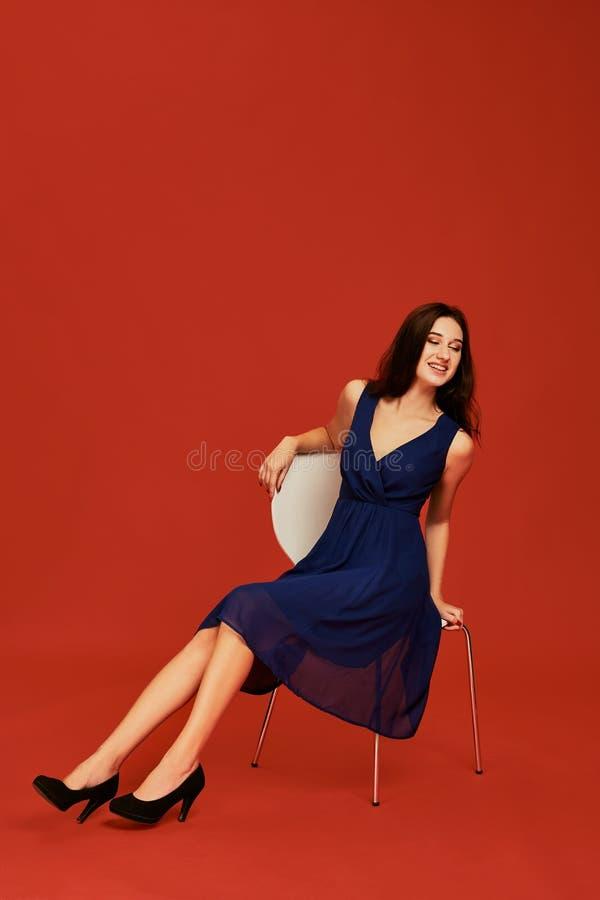 Den härliga unga brunettkvinnan i elegant blå coctailklänning och svarta höga häl poserar för kameran som sitter på fotografering för bildbyråer