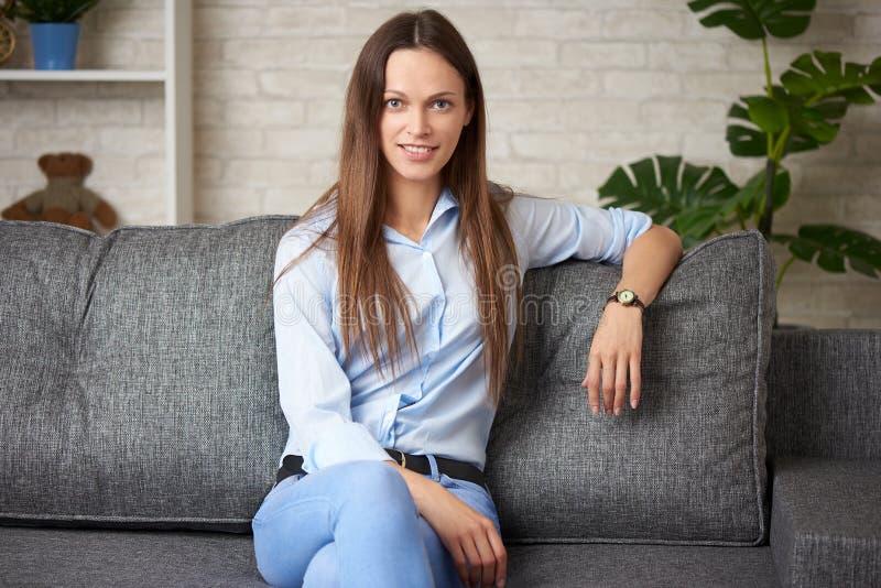 Den härliga unga brunettkvinnan ler sammanträde på en soffa hemma royaltyfri bild