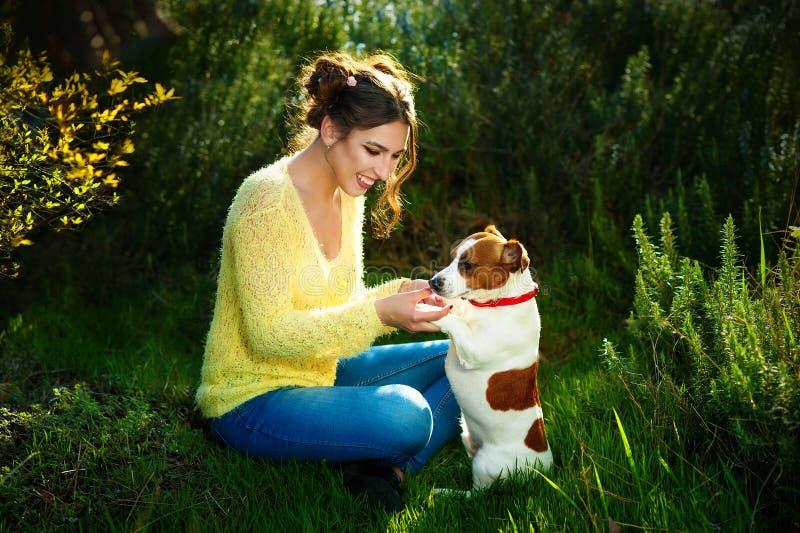 Den härliga unga brunettkvinnan som in tycker om, parkerar utomhus samman med hennes ursnygga Jack Russell terrier - sammanträde  arkivbild
