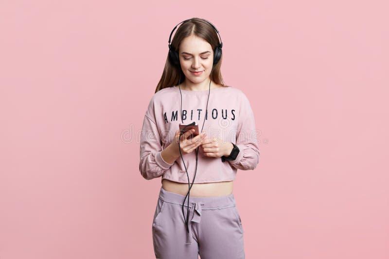 Den härliga unga brunettkvinnlign i hörlurar och smartphone tycker om favorit- musik, har extra- tid Studentförsök att koppla av  royaltyfria foton