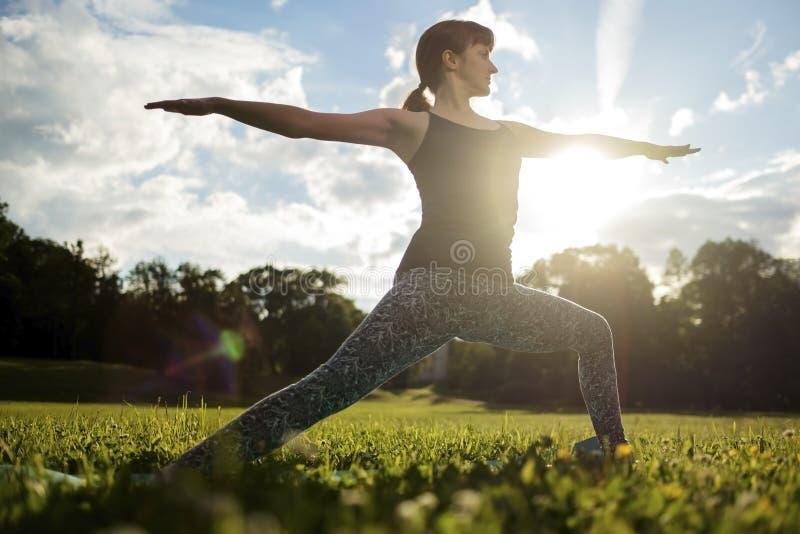 Den härliga unga caucasian kvinnan öva yogaasanaen Virabhadrasana 1 royaltyfri fotografi
