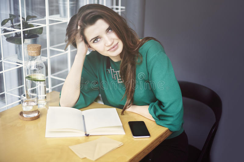 Den härliga unga caucasian kvinnan runt om att sitta som trettio är lyckligt i kafé och att ha frukosten, dricker ren waterÑŽ arkivfoton