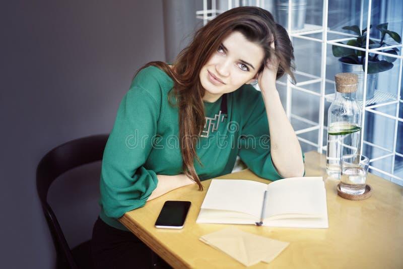 Den härliga unga caucasian kvinnan runt om att sitta som trettio är lyckligt i kafé och att ha frukosten, dricker rent vatten royaltyfria foton
