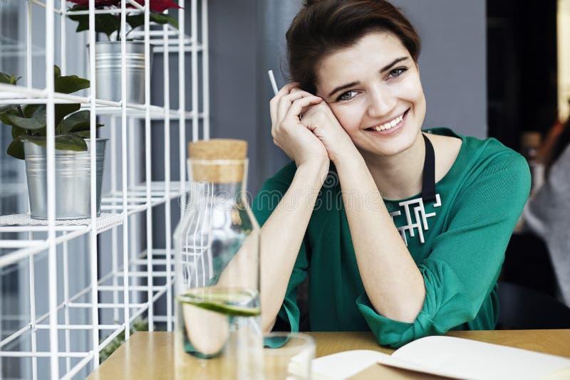Den härliga unga caucasian kvinnan runt om sittande lyckligt le trettio i kafé och att ha frukosten, dricker ren waterÑŽ arkivfoto