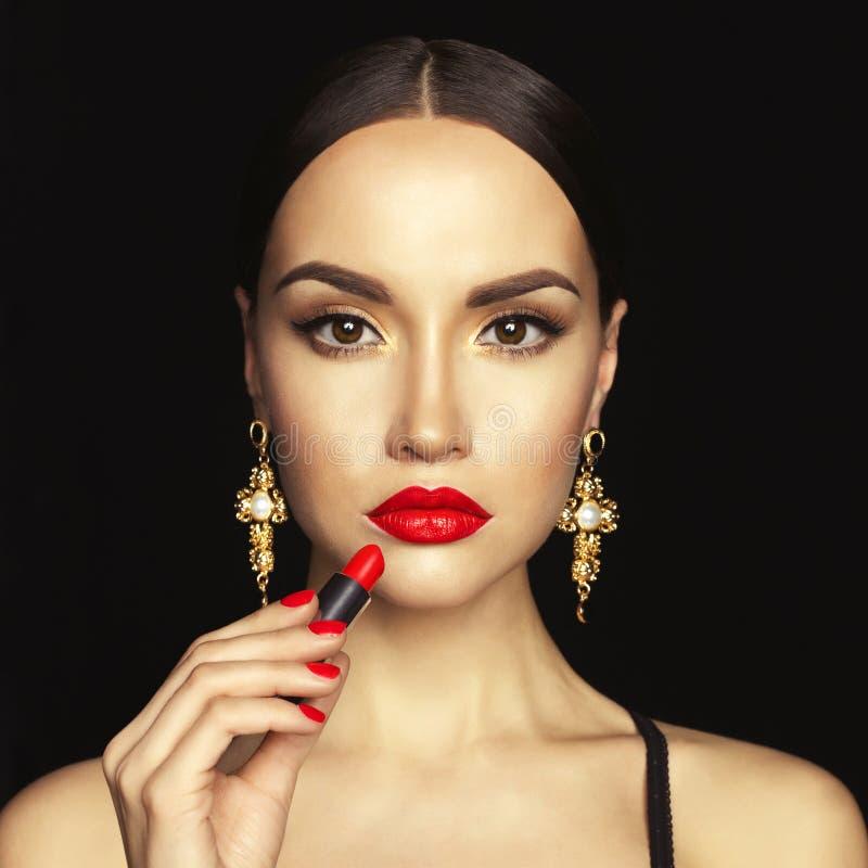 Den härliga unga damen applicerar röd läppstift royaltyfri foto