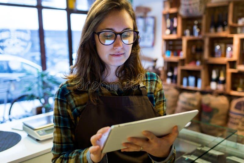Den härliga unga försäljaren som använder hennes digitala minnestavla i organiskt, shoppar fotografering för bildbyråer