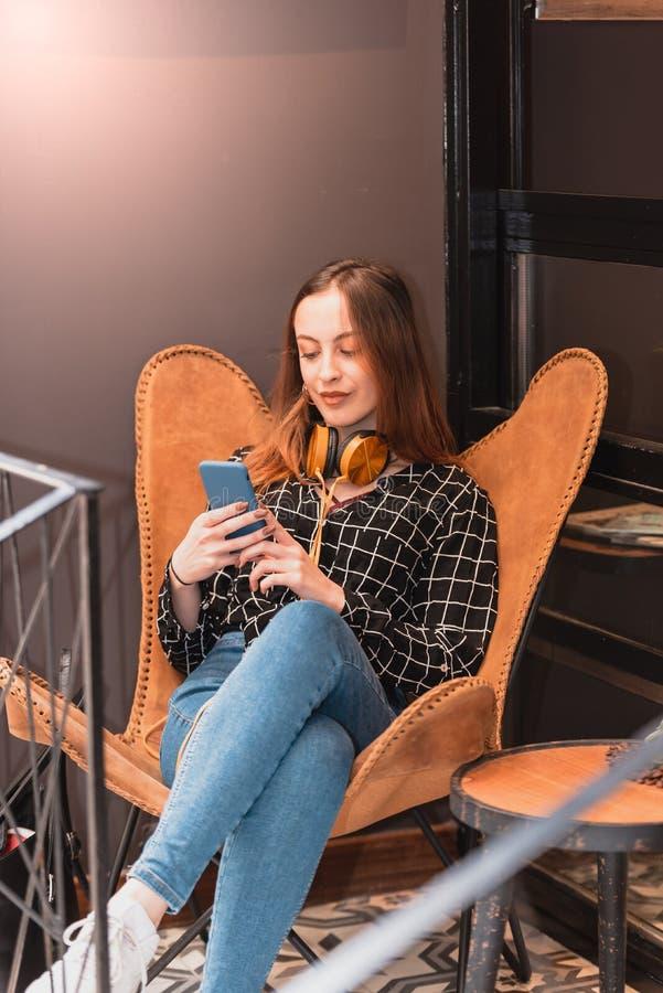 Den härliga unga flickan använder den smarta telefonen och texter arkivbilder