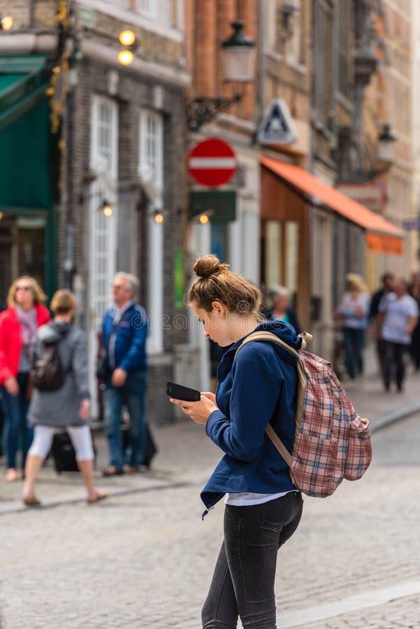 Den härliga unga flickan använder smartphonen royaltyfri fotografi