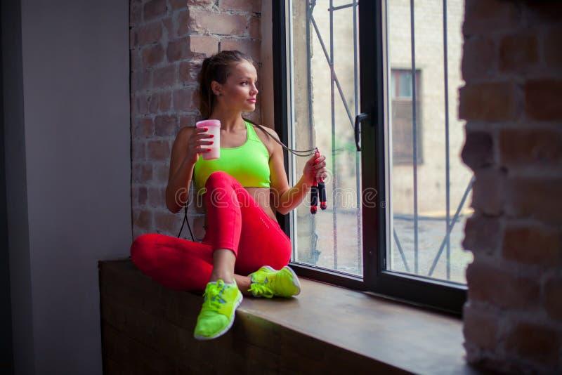 Den härliga unga flickan dricker en konditionsmoothie sunda livsstilar för begrepp arkivbilder