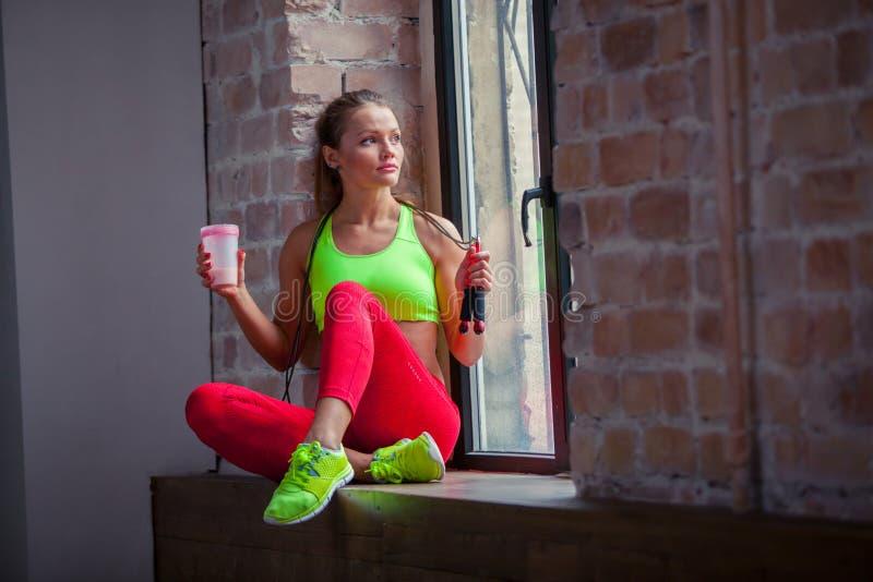 Den härliga unga flickan dricker en konditionsmoothie sunda livsstilar för begrepp royaltyfri foto
