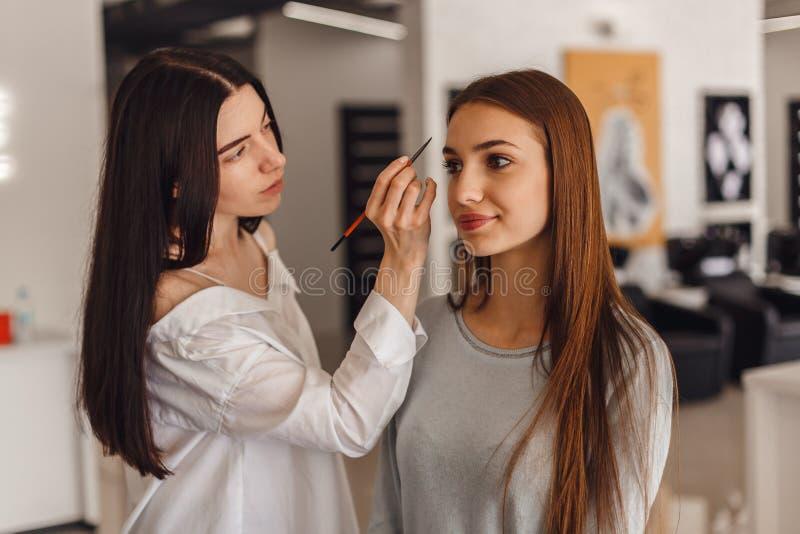 Den härliga unga flickan fick korrigering av ögonbryn i en skönhetsalong arkivbild