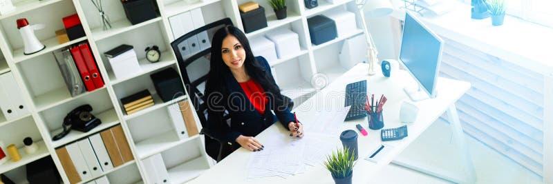 Den härliga unga flickan fyller dokumenten som sitter i kontoret på tabellen royaltyfri fotografi