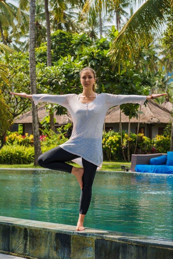 Den härliga unga flickan i damasker och tunika gör yogaövning, meditationen som står poserar på simningen i den Bali ön Indonesie royaltyfri fotografi