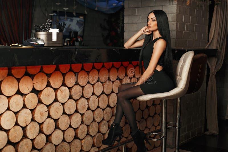 Den härliga unga flickan i en elegant klänning sitter på fotografering för bildbyråer
