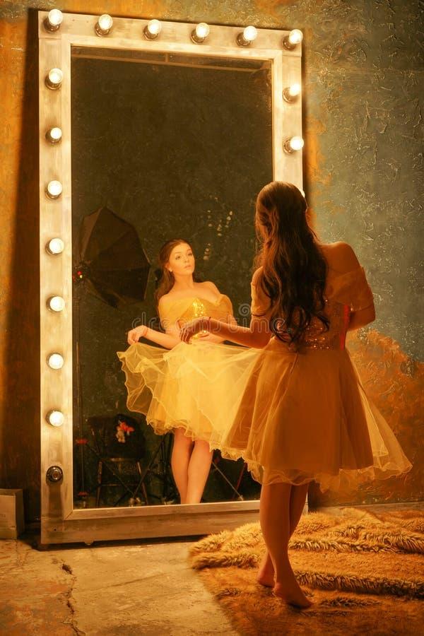 Den härliga unga flickan i en guld- aftonklänning står på en pälsfilt nära en stor spegel i en ram med ljus och blickar in i henn arkivfoton