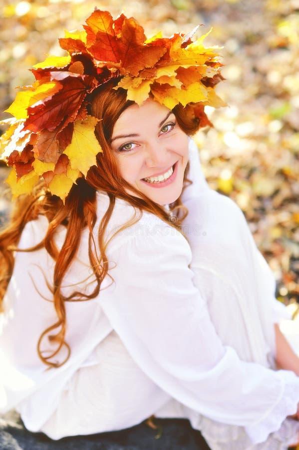 Den härliga unga flickan i en krans från guling lämnar, i vit kläder som sitter på nedgångsidor på en solig dag och skratta royaltyfria bilder