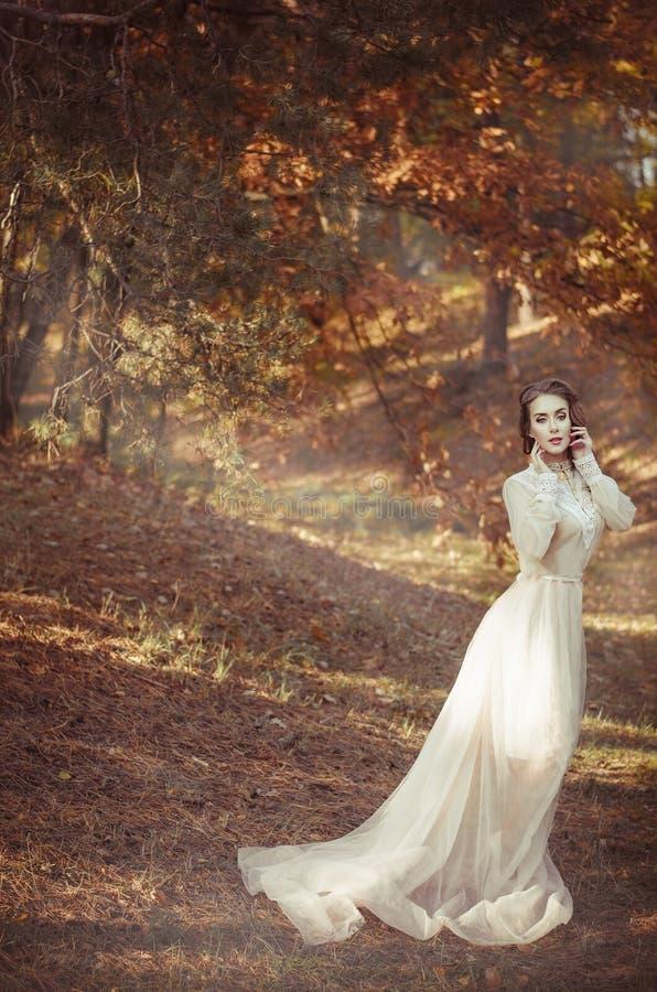 Den härliga unga flickan i en lång försiktig vinkande ljus klänning står i höstskogbruden på en gå arkivbild