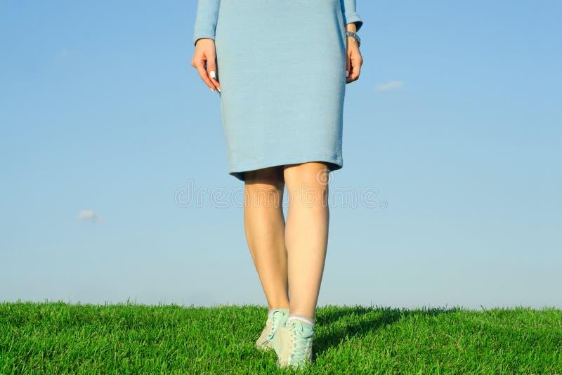 Den härliga unga flickan i gräs för klänningnaturhimmel lägger benen på ryggen royaltyfria bilder