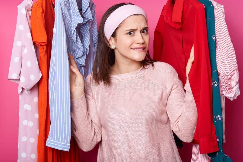 Den härliga unga flickan i rosa skjorta har shopping i modeboutique Den nätta damen väljer klänningen i kläderlager Kvinnafynd royaltyfri bild