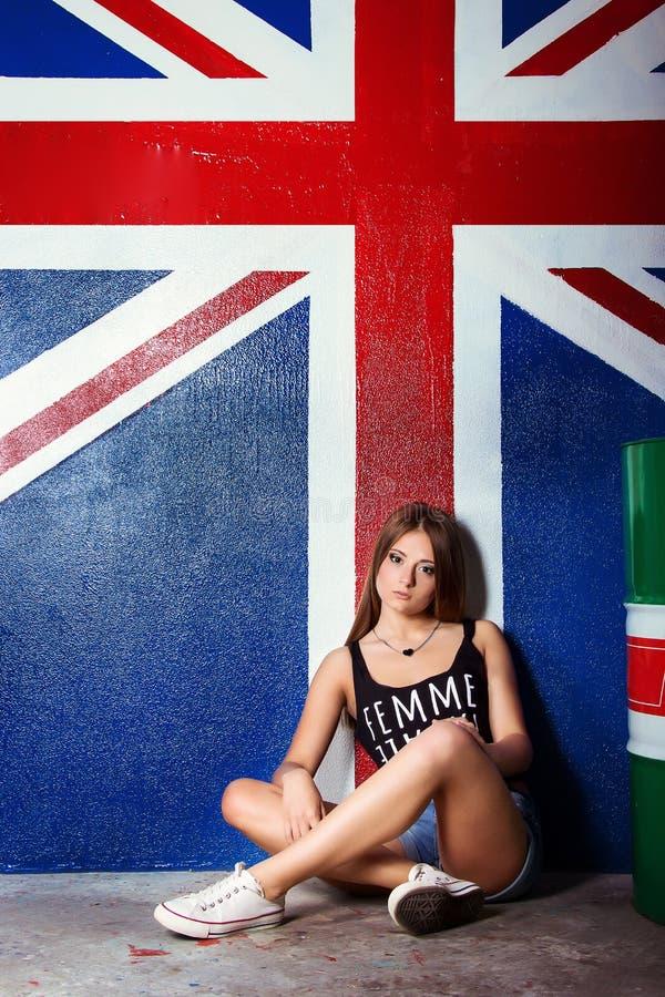Den härliga unga flickan i skor för jeanskortslutningssportar sitter nära trummorna i studion på bakgrunden av flaggan av Britann royaltyfri foto