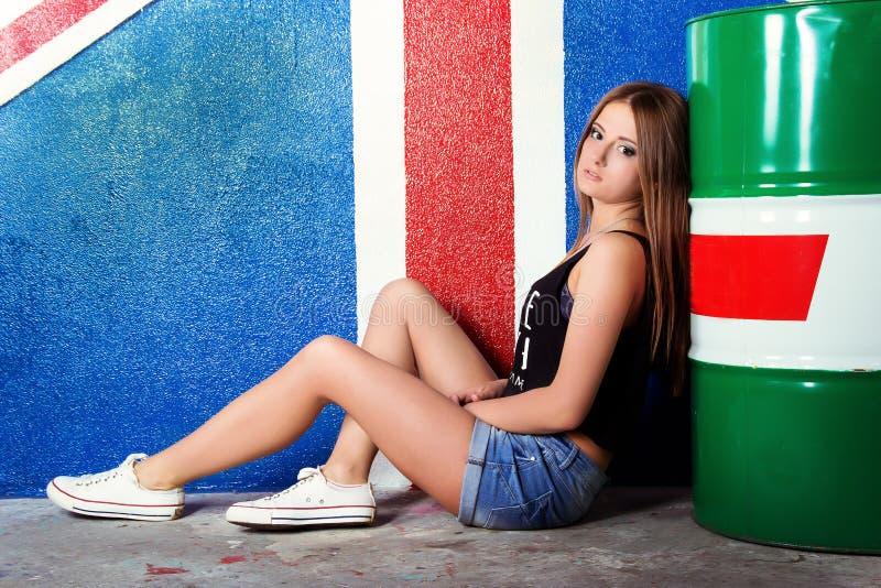 Den härliga unga flickan i skor för jeanskortslutningssportar sitter nära trummorna i studion på bakgrunden av flaggan av Britann royaltyfria bilder