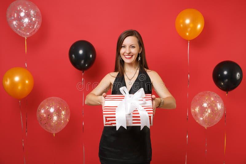 Den härliga unga flickan i den svarta klänningen som ger sig eller mottar som rymmer den röda asken med gåvan, framlägger på ljus royaltyfri fotografi