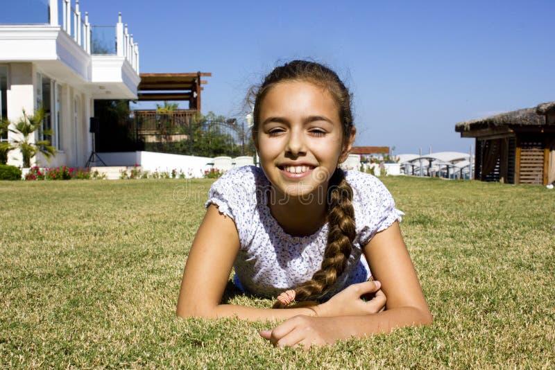 Den härliga unga flickan ligger på en mage på gräset och le royaltyfri fotografi