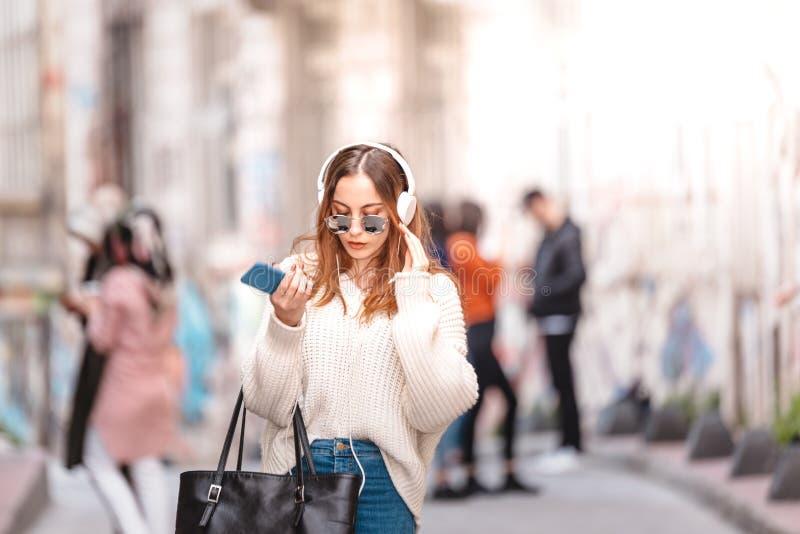Den härliga unga flickan lyssnar musik, medan gå arkivbilder