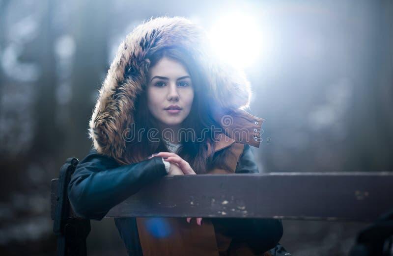 Den härliga unga flickan med brun pälsudde som tycker om vinterlandskapsammanträdet på bänken parkerar in Tonårs- flicka som pose arkivfoton