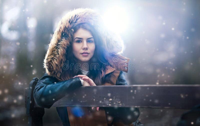 Den härliga unga flickan med brun pälsudde som tycker om vinterlandskapsammanträdet på bänken parkerar in Tonårs- flicka som pose arkivfoto
