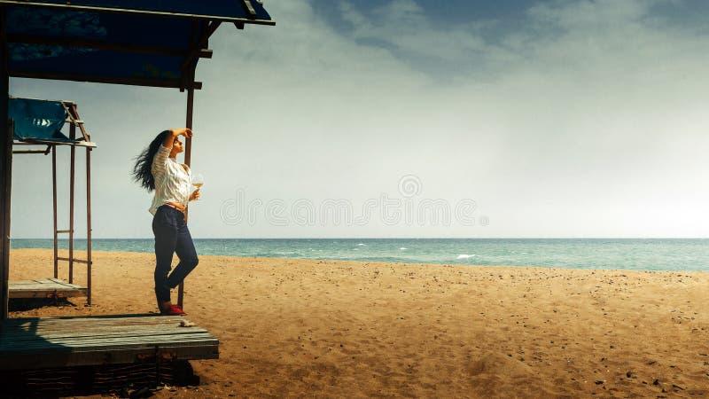 Den härliga unga flickan med ett exponeringsglas av vin står på stranden och tycker om det härliga landskapet Vård- lyckabegrepp  royaltyfria foton