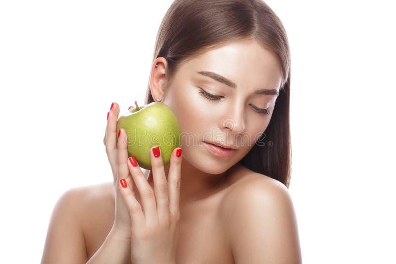 Den härliga unga flickan med ett ljust naturligt smink och gör perfekt hud med äpplet i hennes hand Härlig le flicka arkivfoton