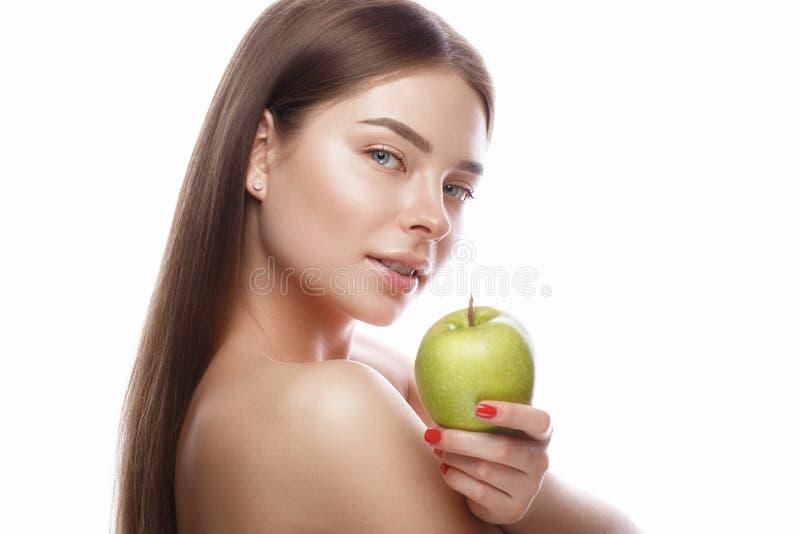 Den härliga unga flickan med ett ljust naturligt smink och gör perfekt hud med äpplet i hennes hand Härlig le flicka arkivbild