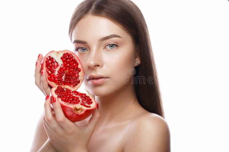 Den härliga unga flickan med ett ljust naturligt smink och gör perfekt hud med granatäpplet i hennes hand Härlig le flicka arkivbild