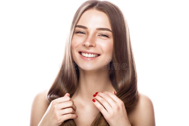 Den härliga unga flickan med ett ljust naturligt smink och gör perfekt hud Härlig le flicka royaltyfri bild